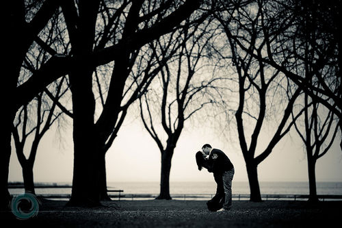 couple kissing amongst trees